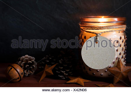 Rustic Christmas Scene With Jar Candle Pine Cones Metals Stars And