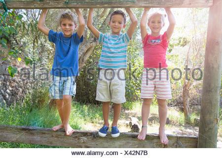 Three children in garden standing on fence - Stock Photo