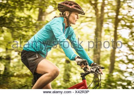 Happy mature female mountain biker speed cycling in forest - Stock Photo