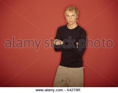 Man, young, blond, poor crosses,  Half portrait  Series, men's portrait, 20-30 years, hairdo, fashionably, Shirt, Longsleeve, nonchalant, casual, expression, self-confidence, self-confidence, gaze camera, indoors, studio, background red - Stock Photo