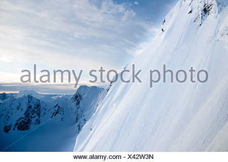Man skiing steep powder on the southwest face of Kickstep Mountain, Turnagain Pass, Kenai Mountains in Southcentral Alaska - Stock Photo