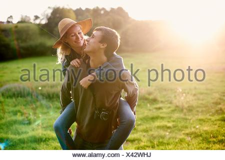 Young man giving girlfriend a piggyback in rural field - Stock Photo