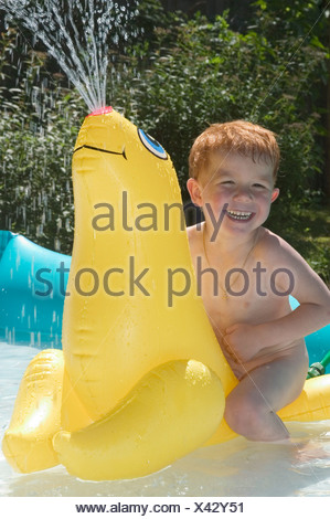 Little boy is playing and splashing with inflatable water animals in her paddling pool in the summertime - Stock Photo