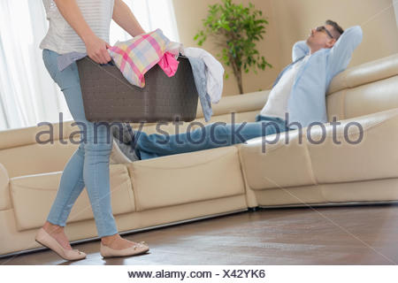 Low section of woman walking with laundry basket while man relaxing on sofa in background - Stock Photo