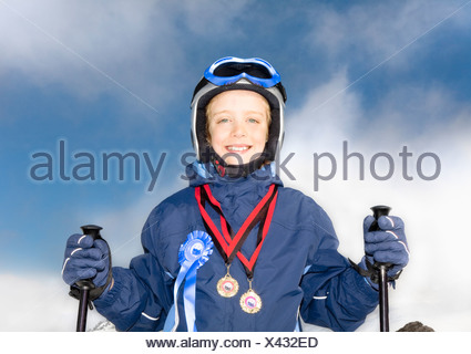 Boy wearing medals and with skis - Stock Photo