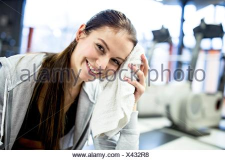 PROPERTY RELEASED. MODEL RELEASED. Portrait young woman wiping her sweat after workout in gym. - Stock Photo