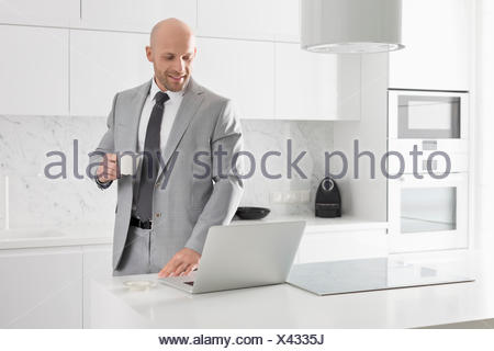 Mid adult businessman having coffee while using laptop in kitchen - Stock Photo