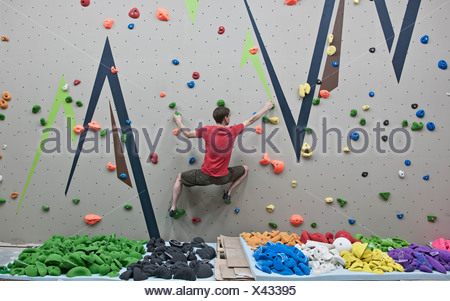Route setter trying bouldering problem at indoor climbing wall - Stock Photo