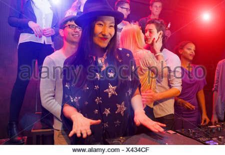 Mid adult woman DJing at party, people dancing in background - Stock Photo