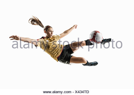 Studio shot of young female soccer player kicking ball mid air - Stock Photo