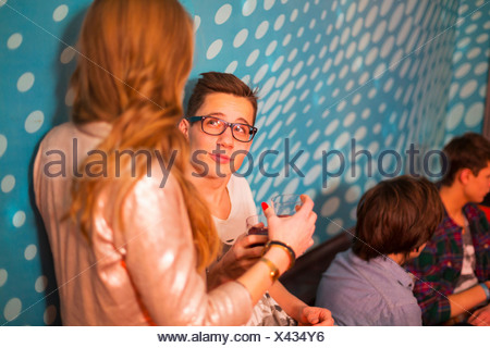 Teenage boy looking up at teenage girl, friends in background - Stock Photo