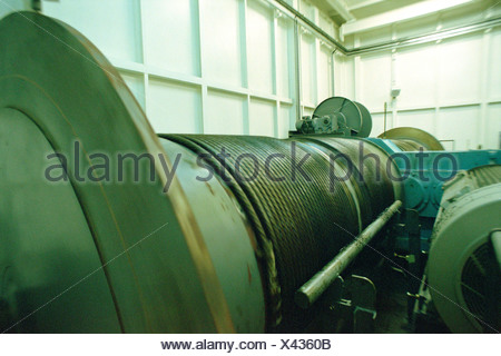 Winding drum with coiled cable in an engine room - Stock Photo