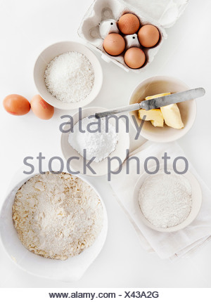 Bowls of sugar, flour, eggs, butter - Stock Photo