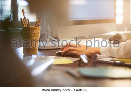 Businesswoman using computer and computer mouse at desk - Stock Photo