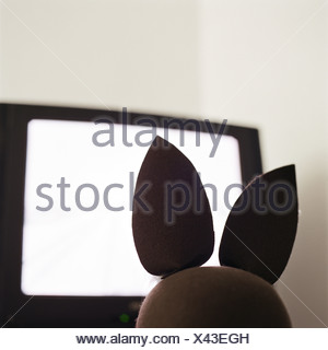Child's bunny rabbit facing television, rear view - Stock Photo