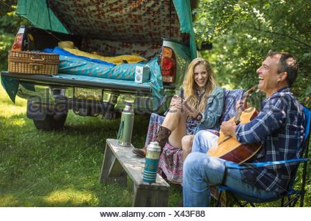 Mature man singing and playing acoustic guitar for girlfriend whilst camping - Stock Photo
