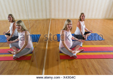 Two pregnant women practicing yoga together in exercise studio - Stock Photo