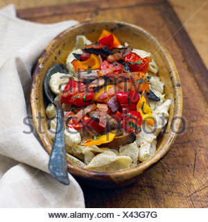 Creamy bacon pasta with roasted vegetables in a serving dish with serving spoon on a wooden surface - Stock Photo