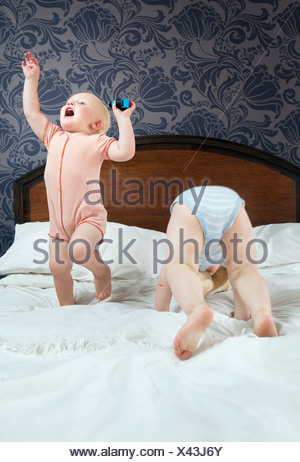 Two baby boys play on a bed - Stock Photo