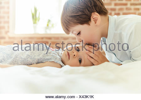 Brother softly kissing his little sister on her forehead - Stock Photo