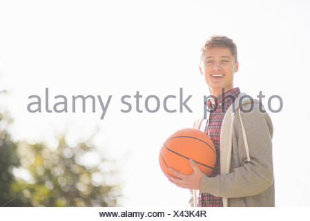 Portrait of smiling young man holding basketball - Stock Photo