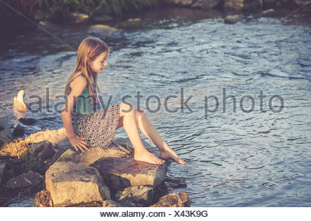 Girl sitting at waterside checking temperature of the water - Stock Photo