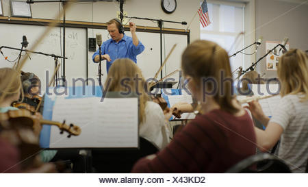 Selective focus view of teacher conducting musicians in band class - Stock Photo