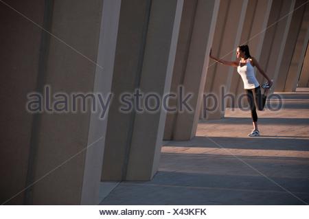Runner stretching on concrete pillar - Stock Photo