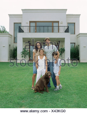 Family and their dog in the garden - Stock Photo