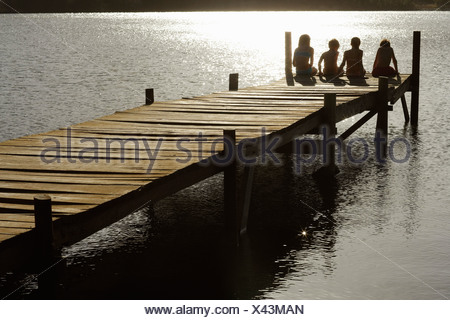 Four children (7-9) sitting on dock by lake, back view. - Stock Photo