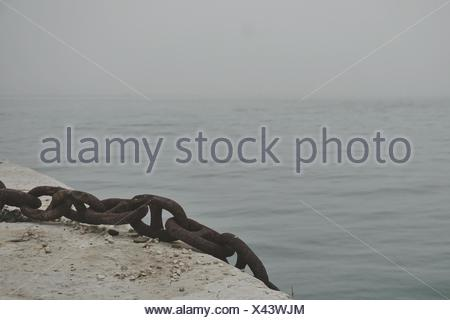 Close-Up Of Rusty Metal Chain On Pier At Sea - Stock Photo