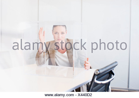 Businesswoman in conference room with transparent cube - Stock Photo