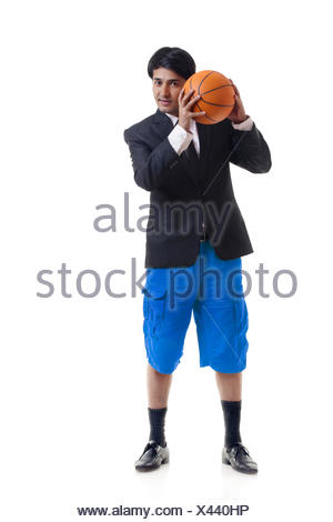 Portrait of young man holding basketball - Stock Photo