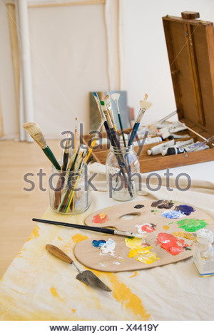 Artist s palette and paintbrushes on table Stock Photo
