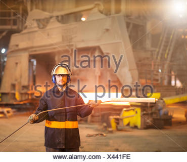 Portrait of steelworker holding sample lance in steelworks - Stock Photo