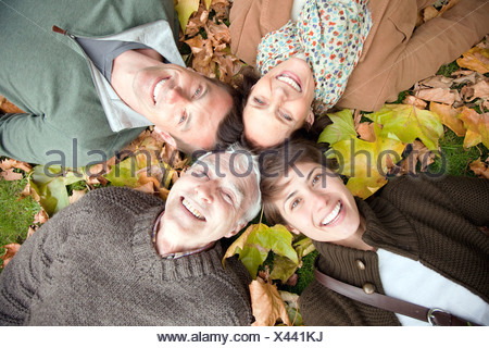 Family lying in autumn leaves in a park - Stock Photo