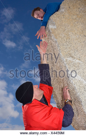 Climber offering hand to fellow climber - Stock Photo