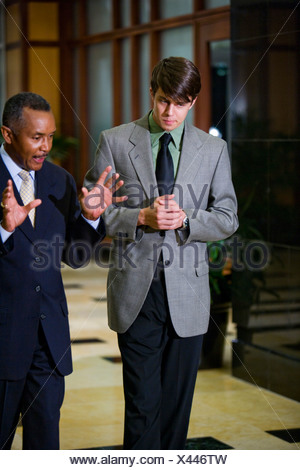 African-American businessman with talking young colleague, walking through lobby - Stock Photo