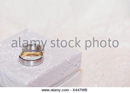 Wedding rings made of gold and platinum with diamonds on white precious jewellery box - Stock Photo