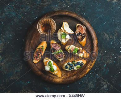 Italian crostini with various toppings and glass of wine on round wooden serving tray over black plywood background, top view - Stock Photo