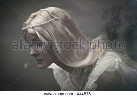 A blonde hair lady with big blue sad eyes looking with sad emotion wearing white dress - Stock Photo