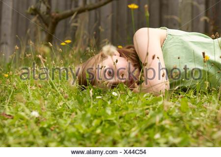 Girl lying on garden grass daydreaming - Stock Photo