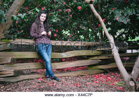 Portrait of a woman standing beside wooden fence, looking sideways - Stock Photo