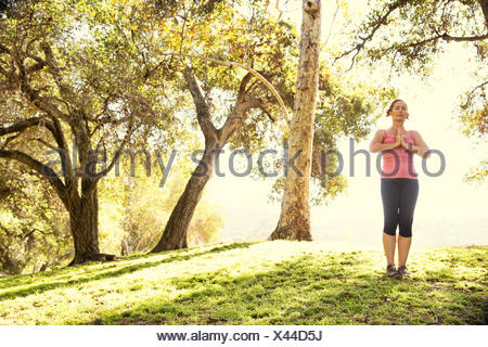 Mature woman in park practicing yoga - Stock Photo
