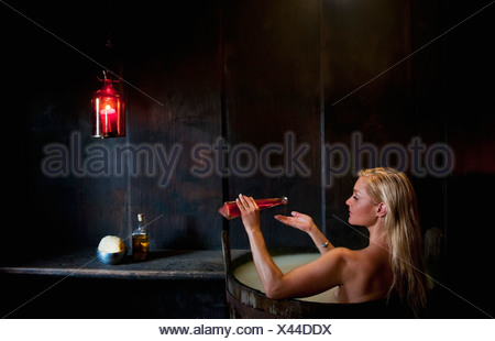 Austria, Salzburg County, Young woman taking bath in wooden tub - Stock Photo