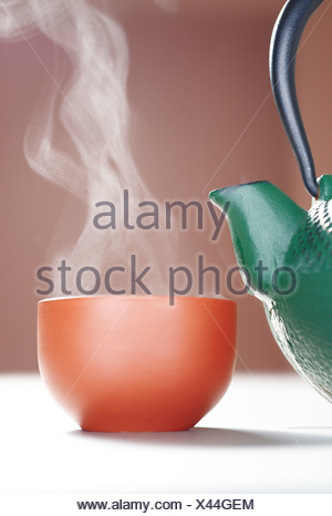 Cast iron teapot with a steaming cup of tea - Stock Photo