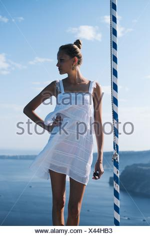 Young woman in sundress against sea - Stock Photo