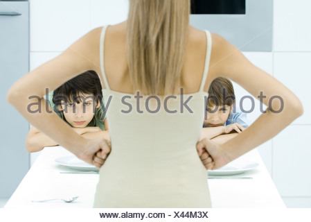 Mother standing with hands on hips in front of two sulking boys, cropped view - Stock Photo