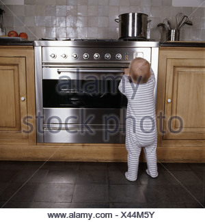 Infant standing by oven in kitchen - Stock Photo