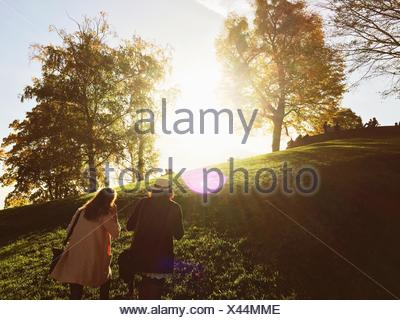 Rear View Of Young Female Friends Climbing Hill In Park - Stock Photo